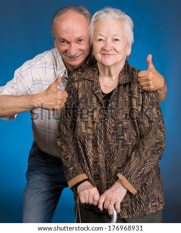 Senior son with old mother on a blue background - stock photo