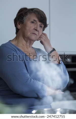 Senior sorrowful woman deep in thought in the kitchen - stock photo