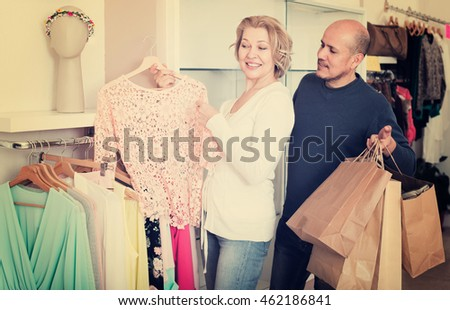Senior spouses buying new blouse in boutique, woman is happy