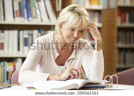 Senior student working in library - stock photo