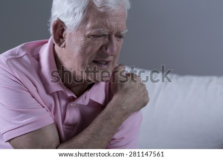 Senior suffering from shoulder pain - stock photo