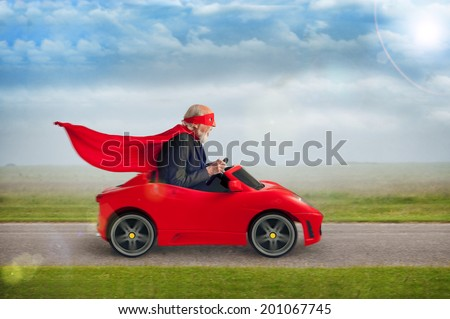 senior superhero with mask and cape driving a toy sports car - stock photo