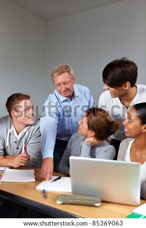 Senior teacher and happy students in school learning - stock photo