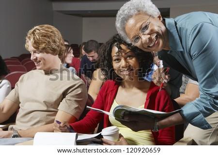 Senior teacher explaining lesson to students in the classroom - stock photo