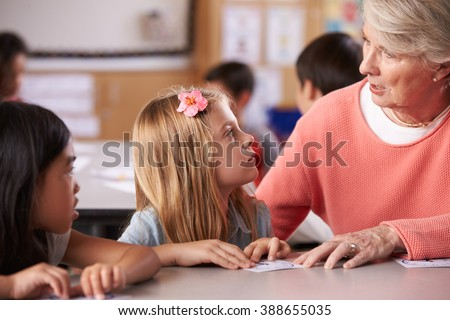 Senior teacher helping pupils in elementary school lesson - stock photo
