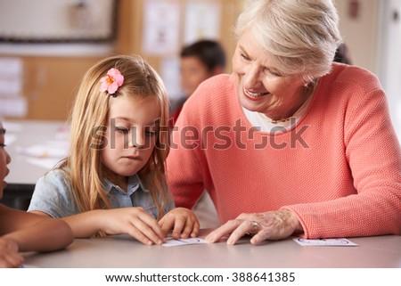 Senior teacher helping schoolgirl in elementary class - stock photo