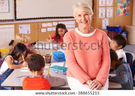 Senior teacher in classroom with elementary school kids - stock photo
