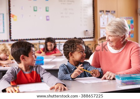 Senior teacher sitting with elementary school kids in class - stock photo