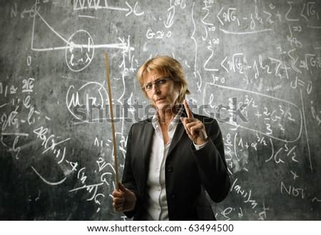 Senior teacher with blackboard on the background - stock photo