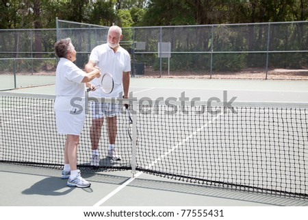 Senior tennis players shake hands over the net.  Wide shot with room for text. - stock photo