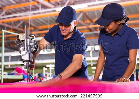 senior textile worker teaching new employee about cutting material - stock photo