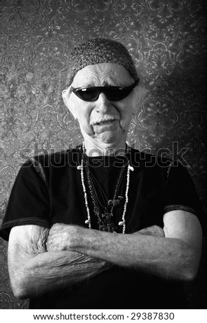 Senior tough guy in knit cap leaning against a wall - stock photo