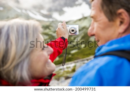 Senior tourist couple hiking and taking selfie at the beautiful mountains - stock photo