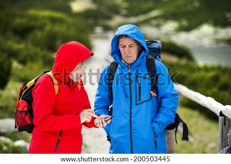 Senior tourist couple hiking at the beautiful mountains in cold weather - stock photo