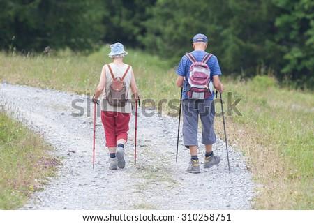 Senior tourist couple hiking at the beautiful mountains, Switzerland - stock photo