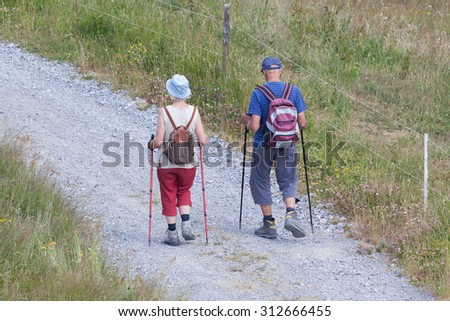 Senior tourist couple hiking at the beautiful mountains, Switzerland - stock photo