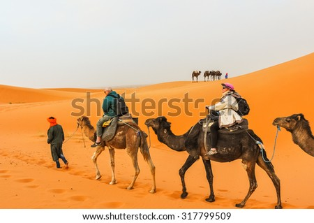 Senior tourists riding camels on Dunes Erg Chebbi near Merzouga, Morocco - stock photo