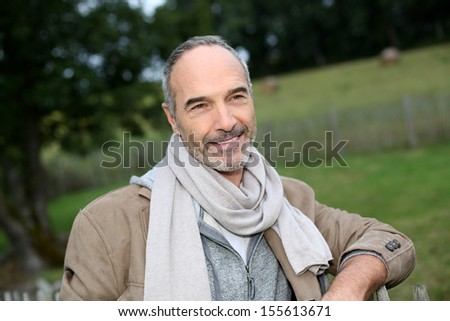 Senior trendy man standing by fence in countryside