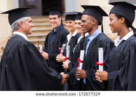 senior university professor handshaking with young graduates - stock photo