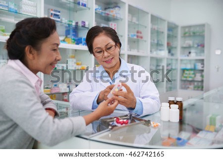 Senior Vietnamese pharmacist and customer discussing medications