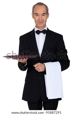 Senior waiter holding empty tray - stock photo