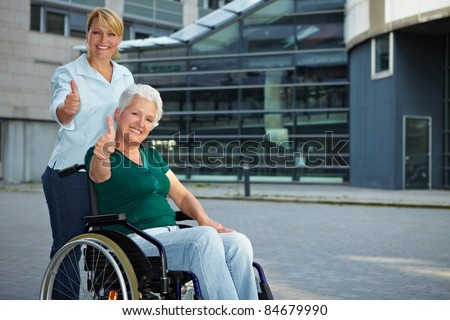 Senior wheelchair driver and nurse holding thumbs up - stock photo