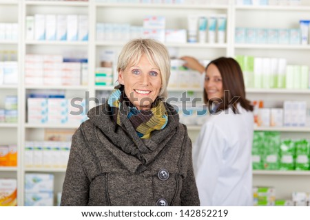 Senior with a scarf in the pharmacy with the pharmacist in the background - stock photo