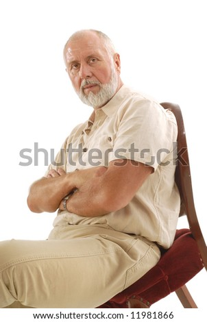 Senior with crossed arms sitting in a plush chair on white background