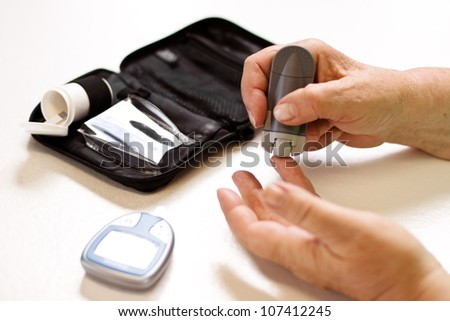 senior with equipment of blood sugar test - stock photo