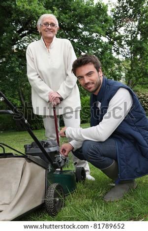 Senior with gardener and lawnmower - stock photo