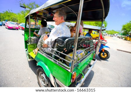 Senior with grandaughter enjoying a fast ride on Bangkok's most popular method of transportation,the '' tuktuk '', Bangkok Thailand - stock photo