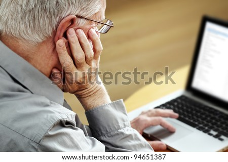 Senior with Laptop, focus on hand - stock photo
