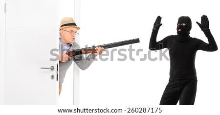 Senior with rifle catching a burglar isolated on white background - stock photo