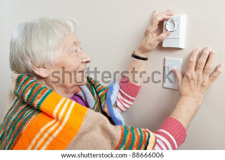 Senior woman adjusting her thermostat - stock photo