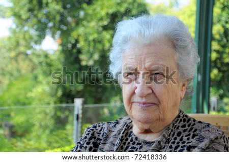 senior woman against tree background - stock photo