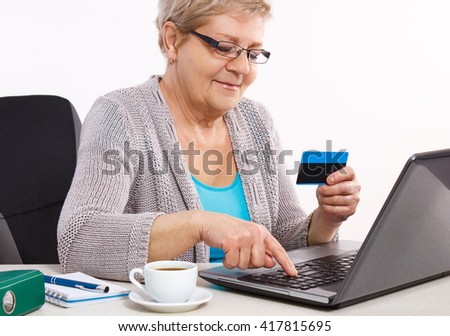 Senior woman, an elderly pensioner with credit card and laptop paying over internet for utility bills or online shopping, surfing internet, typing on computer keyboard - stock photo