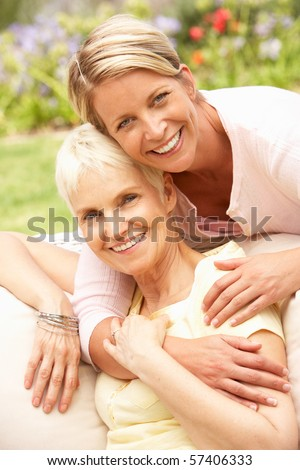 Senior Woman And Adult Daughter Relaxing In Garden - stock photo