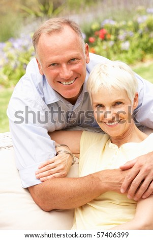 Senior Woman And Adult Son Relaxing In Garden - stock photo