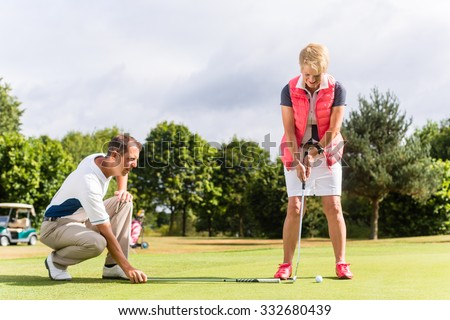 Senior woman and golf pro practicing their sport - stock photo