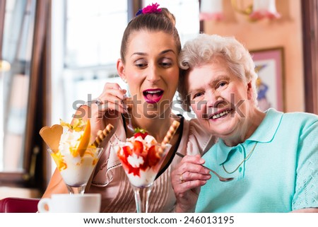 Senior woman and granddaughter having fun eating ice cream sundae in cafe - stock photo