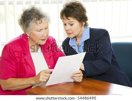 Senior woman and her broker or consultant going over paperwork together. - stock photo