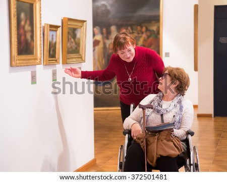 Senior woman and her handicapped female friend whatching art works on exhibition - stock photo
