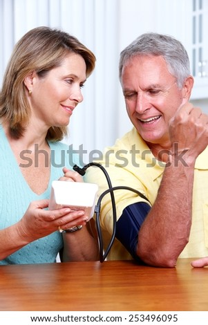 Senior woman and man measuring blood pressure. - stock photo
