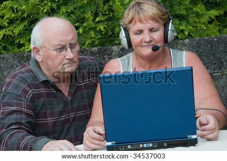 senior woman and man on laptop outside - stock photo