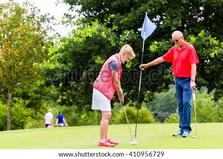 Senior woman and man playing golf putting on green - stock photo