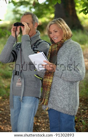 Senior woman and senior man watching through binoculars - stock photo