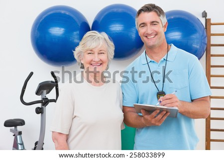 Senior woman and trainer smiling at camera in fitness studio - stock photo