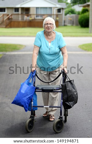 senior woman and walker overloaded with shopping bags - stock photo