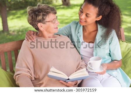 Senior woman and young carer being friends - stock photo