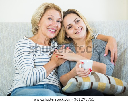 Senior woman and young female with cup of tea at home